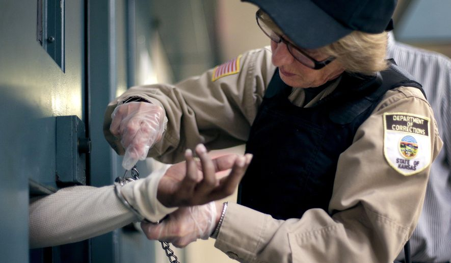 In this photo taken Tuesday, Dec. 8, 2015, corrections officer Cynthia Miller handcuffs an inmate before he is transported from a segregation unit at the Ellsworth Correctional Facility in Ellsworth, Kan. Low wages among Kansas corrections officers are causing many to leave the field, leaving about 9 percent of the positions in the state's prisons unfilled. (AP Photo/Charlie Riedel)
