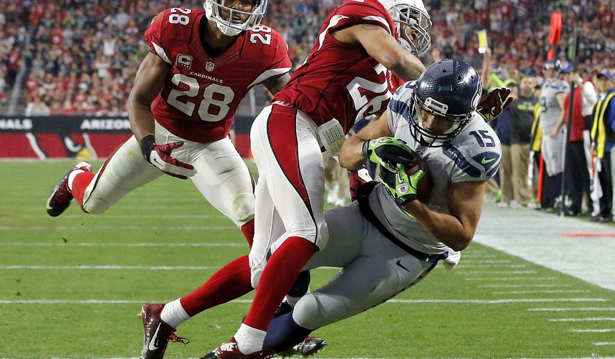Seattle Seahawks wide receiver Jermaine Kearse (15) falls into the end zone for a touchdown as Arizona Cardinals free safety Rashad Johnson (26) and cornerback Justin Bethel (28) defend during the first half of an NFL football game, Sunday, Jan. 3, 2016, in Glendale, Ariz. (AP Photo/Ross D. Franklin)