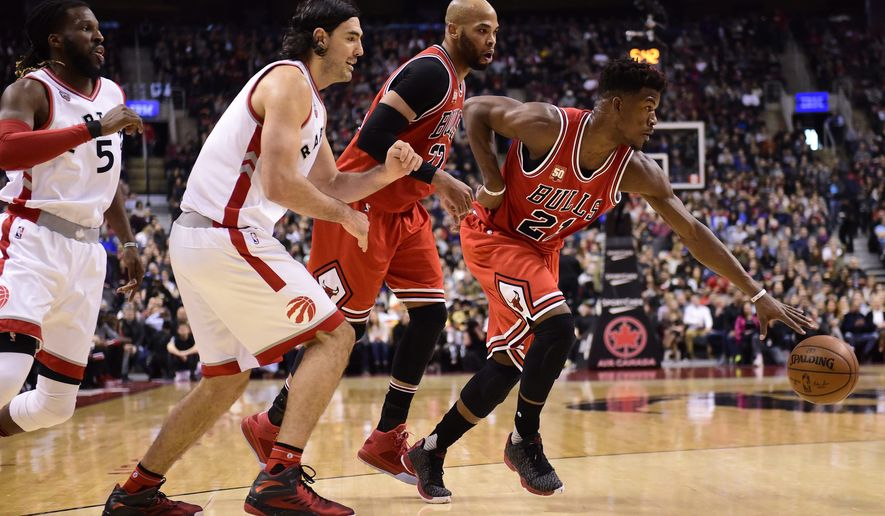 Chicago Bulls' Jimmy Butler, right, dribbles away from Toronto Raptors' Luis Scola, second from left, and DeMarre Carroll, left, as Bulls' Taj Gibson looks on during first-half NBA basketball game action in Toronto, Sunday, Jan. 3, 2016. (Frank Gunn/The Canadian Press via AP) MANDATORY CREDIT