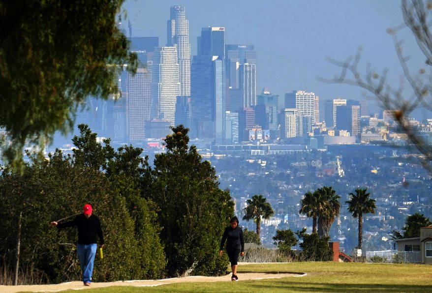Hikers walk along a path at the Kenneth Hahn State Recreation Area near downtown Los Angeles on Sunday, Jan. 3, 2016. Southern California is bracing for a series of storms expected to begin late Sunday that could last all week. (AP Photo/Richard Vogel)