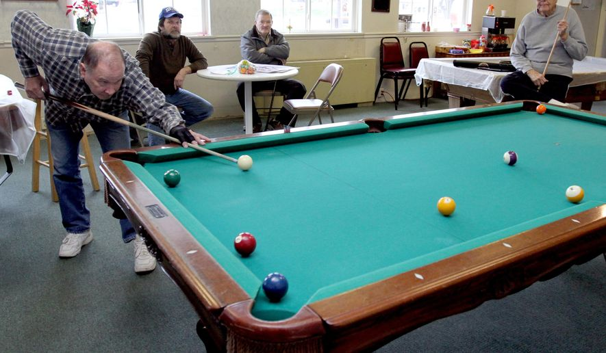 Gene Coffield, left, sets up a shot Tuesday, Dec. 29, 2015, during a billiards game with Merl Mingus, right, as Mike Beauchamp, second from left, and Mike Harl, look on at the Munday Activity Center in Owensboro, Ky. The four men are retired and met at the center, where they play pool and occasionally eat meals. Munday Activity Center Executive Director Dana Peveler said there are probably 600 games of pool played there each month. (Greg Eans/The Messenger-Inquirer via AP)