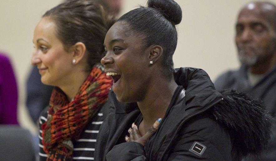 Defendant Angela Gipson, front, reacts, while talking with Judge Michael Distel, near Erika Mariglia, as part of Community Outreach Court at Mel Trotter Ministries on Wednesday, Nov. 18, 2015. The court is designed to help the homeless and those in poverty resolve their non-violent legal issues in a way that takes their special circumstances into account. Mariglia is from Mel Trotter. (Cory Morse/The Grand Rapids Press via AP)