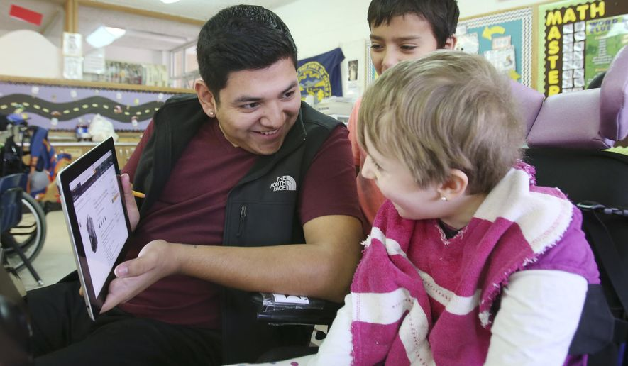 ADVANCE FOR THE WEEKEND OF JAN. 3 - In this Dec. 17, 2015 photo, Paraeducator Kevin Medrano works with Harvard Elementary fourth graders Maggie Fields, far right, and Alexander Espinoza during a math class in Harvard, Neb. The middle child of seven siblings, Medrano, a 21-year-old paraeducator at Harvard Public Schools, is fulfilling the dying wish of his mother, Ruth Elizabeth Guevara, by rearing his two youngest siblings, Samantha (Sam), 17, and Oscar, 14, on his own. (Laura Beahm/The Hastings Tribune via AP) MANDATORY CREDIT