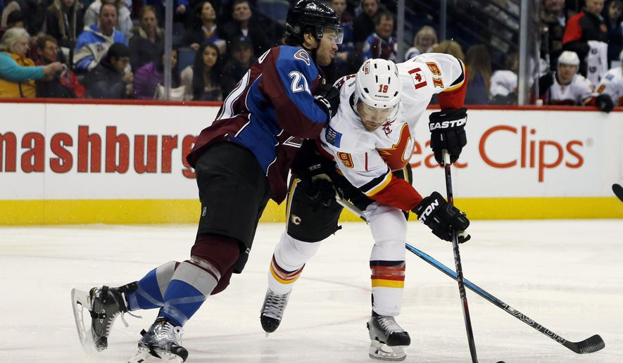 Calgary Flames right wing David Jones, right, directs a shot past Colorado Avalanche defenseman Zach Redmond in second period of an NHL hockey game Saturday, Jan. 2, 2016, in Denver. (AP Photo/David Zalubowski)