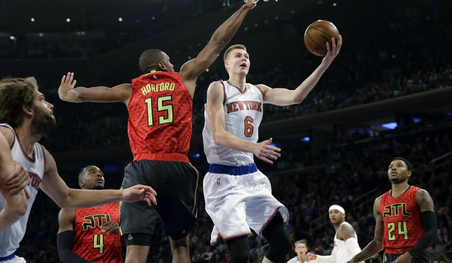 New York Knicks' Kristaps Porzingis (6) drives past Atlanta Hawks' Al Horford (15) for a shot during the first half of the NBA basketball game, Sunday, Jan. 3, 2016 in New York. (AP Photo/Seth Wenig)