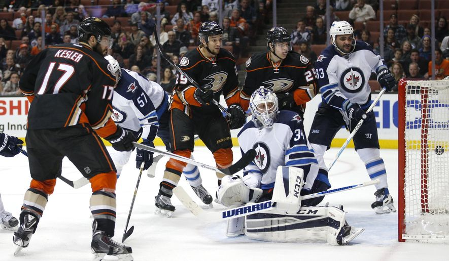 Anaheim Ducks' Ryan Kesler (17) scores against Winnipeg Jets goalie Michael Hutchinson (34) as teammate Chris Stewart (29) and Mike Santorelli (25) watch during the second period of an NHL hockey game, Sunday, Jan. 3, 2016, in Anaheim, Calif. (AP Photo/Jae C. Hong)