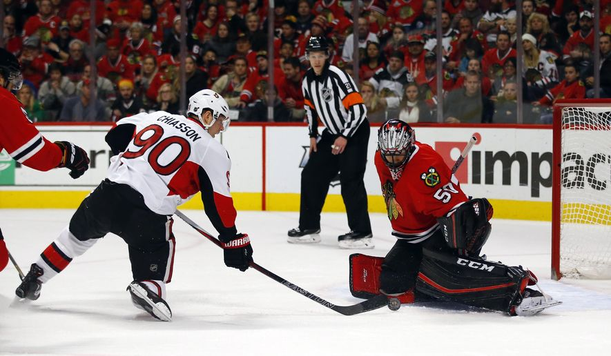 Chicago Blackhawks goalie Corey Crawford (50) stops the shot of Ottawa Senators right wing Alex Chiasson (90) during the first period of an NHL hockey game Sunday, Jan. 3, 2016, in Chicago. (AP Photo/Jeff Haynes)