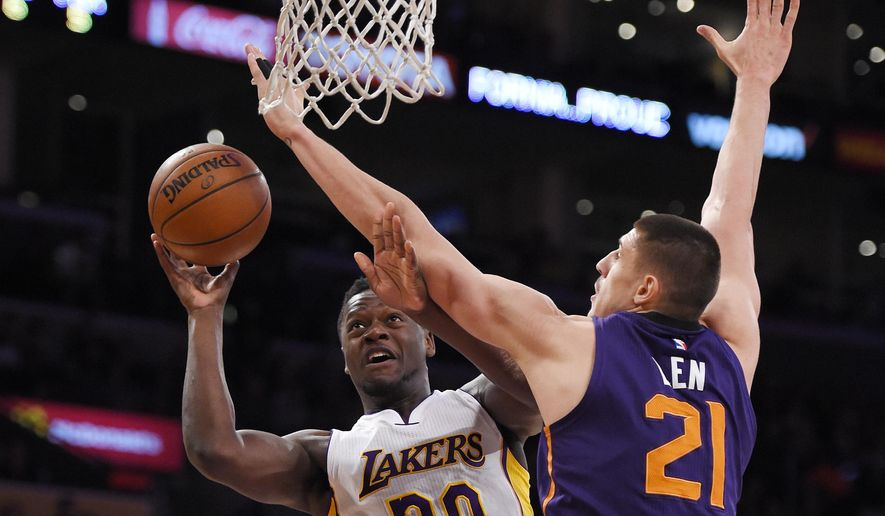 Los Angeles Lakers forward Julius Randle, left, shoots as Phoenix Suns center Alex Len, of Ukraine, defends during the first half of an NBA basketball game, Sunday, Jan. 3, 2016, in Los Angeles. (AP Photo/Mark J. Terrill)