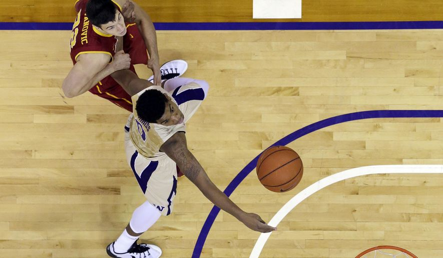 Washington's Marquese Chriss, right, gets a shot off in front of Southern Cal's Nikola Jovanovic during the first half of an NCAA college basketball game Sunday, Jan. 3, 2016, in Seattle. (AP Photo/Elaine Thompson)