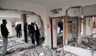 Palestinians stand inside a house that was demolished by the Israeli military in the east Jerusalem neighborhood of Jabal Mukaber, Monday, Jan. 4, 2016. The Israeli military says forces are demolishing and sealing off the Jerusalem homes of two Palestinians involved in deadly attacks against Israelis in the city last year. Both attackers were shot and killed at the scene. (AP Photo/Mahmoud Illean)
