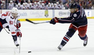 Columbus Blue Jackets' Jack Johnson, right, takes a shot as Washington Capitals' Evgeny Kuznetsov, of Russia, defends during overtime of an NHL hockey game Saturday, Jan. 2, 2016, in Columbus, Ohio. The Blue Jackets won 5-4 in a shootout. (AP Photo/Jay LaPrete)