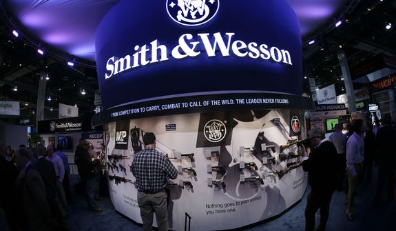 In this Tuesday, Jan. 14, 2014, file photo, trade show attendees examine handguns and rifles in the Smith & Wesson display boot at the Shooting Hunting and Outdoor Tradeshow, in Las Vegas. With all major markets in a severe sell-off Monday, Jan. 4, 2016, shares of companies that make guns surged as new data pointed to strong sales at the close of 2015, a year marked by mass shootings in Paris and California, and new political pressure to tighten regulations. Shares of Smith & Wesson Holding Corp. rose almost 6 percent Monday, one of the biggest percentage gains over the past year for the gunmaker. Its shares hit an all-time high two weeks earlier. (AP Photo/Julie Jacobson, File)