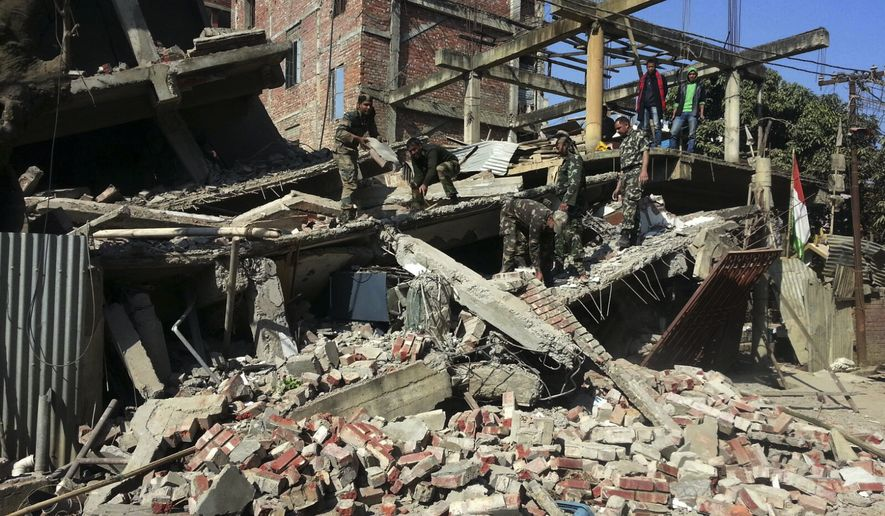 Indian soldiers remove debris from a house that collapsed in an earthquake in Imphal, capital of the northeastern Indian state of Manipur, Monday, Jan. 4, 2016. A 6.7 magnitude earthquake hit India's remote northeast region before dawn on Monday. (AP Photo/Worshon Ngashangva)
