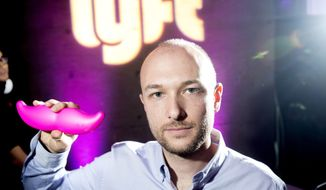 """In this Monday, Jan. 26, 2015, file photo, Logan Green, co-founder and chief executive officer of Lyft, displays his company's """"glowstache"""" during a launch event in San Francisco. On Monday, Jan. 4, 2016, General Motors Co. announced it is investing $500 million in ride-sharing company Lyft Inc. GM gets a seat on Lyft's board as part of the partnership, which could speed the development of on-demand, self-driving cars. (AP Photo/Noah Berger, File)"""