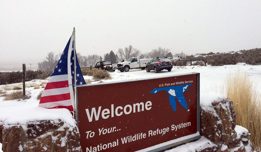 ADDS DETAILS OF SOME VEHICLES SEEN AT THE ENTRANCE - An sign of the National Wildlife Refuge System is seen at an entry of the wildlife refuge, where some vehicles are seen used to block access to the inside of the refuge, about 30 miles southeast of Burns, Ore., Sunday, Jan. 3, 2016. Armed protesters are occupying a building at the national wildlife refuge and asking militia members around the country to join them. The protesters went to Malheur National Wildlife Refuge on Saturday following a peaceful rally in support of two Oregon ranchers facing additional prison time for arson. (Les Zaitz/The Oregonian via AP) MANDATORY CREDIT