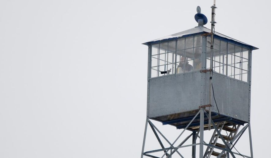 Protesters watch from a watch tower at the National Wildlife headquarters in Burns on Sunday, Jan 3, 2016. Armed protesters took over the Malheur National Wildlife Refuge south of Burns on Saturday after participating in a peaceful rally over the prison sentences of local ranchers Dwight and Steven Hammond. The decision to send the man back to prison generated controversy and is part of a decades-long dispute between some Westerners and the federal government over the use of public lands. (Mark Graves/The Oregonian via AP)