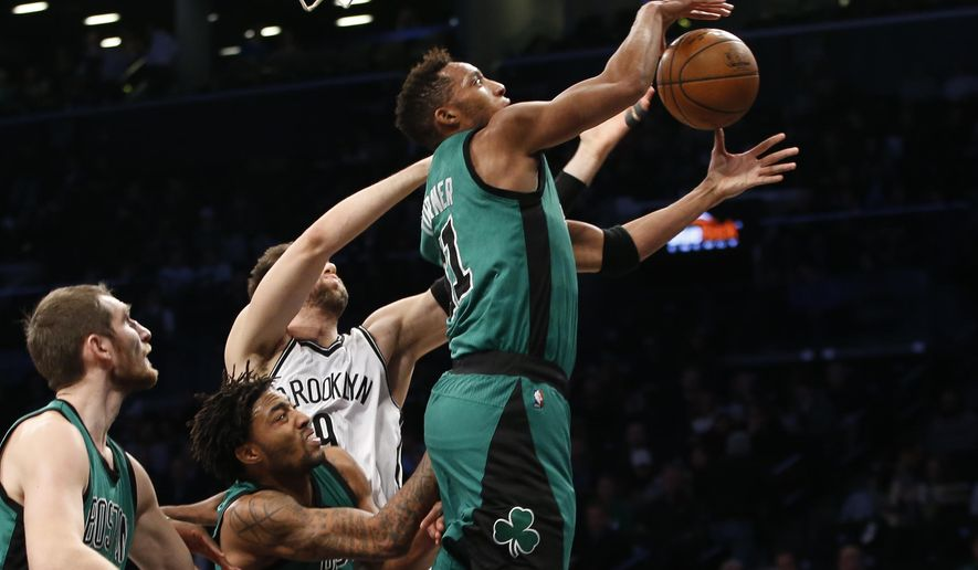 Boston Celtics guard Evan Turner (11) grabs a rebound in front of Brooklyn Nets center Andrea Bargnani (9) in the first half of an NBA basketball game, Monday, Jan. 4, 2016, in New York. (AP Photo/Kathy Willens)