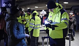 A passenger has her ID checked at the train station Copenhagen International Airport in Kastrup to prevent illegal migrants entering Sweden  on Monday Jan. 4, 2016. The station is the last stop before crossing the Oresund Bridge into Sweden. Sweden requires train companies with service across a bridge-and-tunnel link from Denmark to refuse passengers without ID. (Tariq Mikkel Khan/Polfoto via AP)