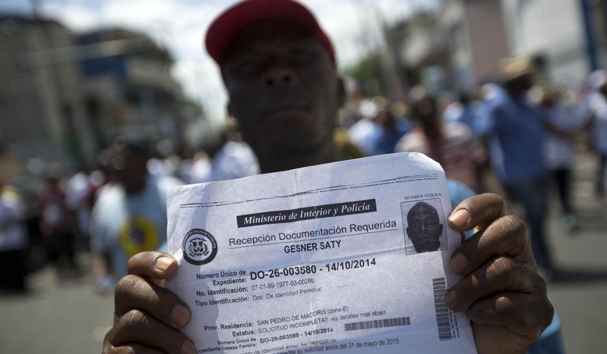 FILE - In this July 21, 2015, file photo, deported Haitian man holds up his document that confirms he turned in paperwork to apply for legal residency in the Dominican Republic during a march to the prime minister's office to protest the DR's deportation of Haitians in Port-au-Prince, Haiti. The sharply uneven situation for non-citizens stems from a 2013 ruling by the Dominican Constitutional Court in a decades-long dispute over who is entitled to citizenship.  (AP Photo/Dieu Nalio Chery, File)