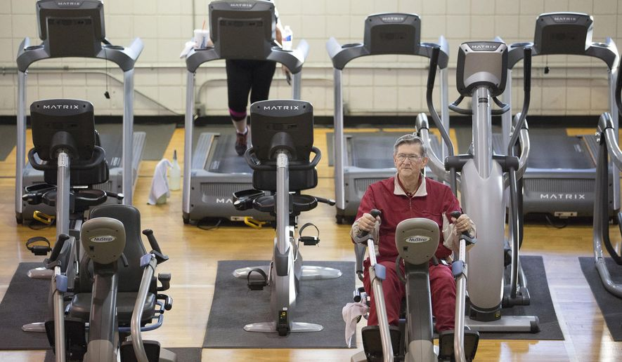 In this photo taken Dec. 22, 2015, Glendon Bassett does a cardio workout at the Family YMCA in Hot Springs, Ark. Bassett, a retired chemical engineer, says he can vouch for the teamwork approach Medicare is promoting. Earlier this year, a primary care team at SAMA Healthcare in El Dorado, Arkansas, prevented what Bassett feared would turn into an extended hospitalization. It started with a swollen leg.  (AP Photo/Evan Lewis)