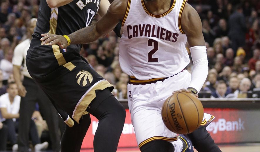 Cleveland Cavaliers' Kyrie Irving (2) drives past Toronto Raptors' Jonas Valanciunas (17), from Lithuania, in the first half of an NBA basketball game, Monday, Jan. 4, 2016, in Cleveland. (AP Photo/Tony Dejak)
