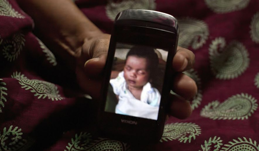 In this Nov. 4, 2015, photo, Amita Parmar, 30, displays a photograph of a South African child she was a surrogate for, in Anand, India. The Indian government recently banned surrogate services for foreigners and ordered fertility clinics to stop the practice of hiring Indian women to bear children for them. (AP Photo/Allison Joyce) ** FILE **
