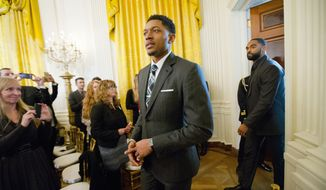 Washington Wizards basketball players Bradley Beal, center, and Alan Anderson, right, arrive in the East Room of the White House in Washington, Tuesday, Jan. 5, 2016, to listen to President Barack Obama talk about steps his administration is taking to reduce gun violence. Also on stage are stakeholders, and individuals whose lives have been impacted by the gun violence. (AP Photo/Pablo Martinez Monsivais)