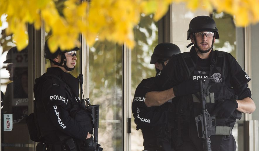 FILE - In this Oct. 21, 2012 file photo, police stand with guns drawn at the entrance to Brookfield Square Mall across from the scene of a shooting at Azana Salon in Brookfield, Wis. President Barack Obama's moves to license more private gun sellers and do background checks on buyers will have the greatest impact on the fast-growing and largely unregulated world of online sales. But it's not clear that the steps will transform the broader gun market, and even the White House says it can't predict how much good it will do. Online transactions have included weapons later used in high-profile mass shootings, including the 2012 mass shooting in Brookfield, Wisconsin. (AP Photo/Tom Lynn, File)
