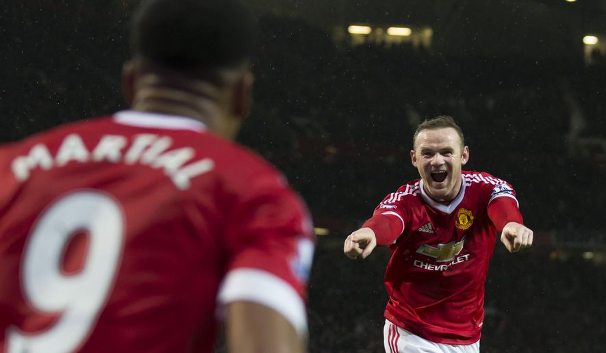 Manchester United's Wayne Rooney, right, celebrates with teammate Anthony Martial after scoring during the English Premier League soccer match between Manchester United and Swansea City at Old Trafford Stadium, Manchester, England, Saturday, Jan. 2, 2016. (AP Photo/Jon Super)