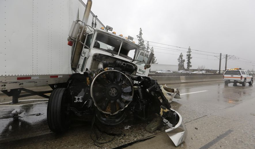 Authorities investigate a multi-vehicle crash involving a semi-truck in the westbound lane of Foothill 210 Freeway at Sierra Madre Blvd., Tuesday, Jan. 5, 2016, in Pasadena, Calif. Persistent wet conditions could put some Los Angeles County communities at risk of flash flooding along with mud and debris flows, especially in wildfire burn areas. El Nino storms lined up in the Pacific, promising to drench parts of the West for more than two weeks and increasing fears of mudslides and flash floods in regions stripped bare by wildfires. (AP Photo/Damian Dovarganes)