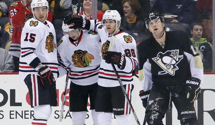 Chicago Blackhawks' Artemi Panarin, second from left, celebrates his goal with teammates Artem Anisimov (15) and Patrick Kane (88) as Pittsburgh Penguins' Ben Lovejoy (12) skates back to his bench during the second period of an NHL hockey game in Pittsburgh, Tuesday, Jan. 5, 2016. (AP Photo/Gene J. Puskar)