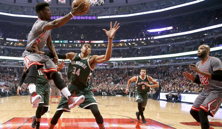 Chicago Bulls guard Jimmy Butler, left, passes the ball past Milwaukee Bucks forward Giannis Antetokounmpo (34) to Taj Gibson during the first half of an NBA basketball game Tuesday, Jan. 5, 2016, in Chicago. (AP Photo/Charles Rex Arbogast)