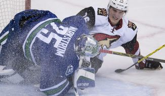 Arizona Coyotes center Laurent Dauphin (76) crashes into Vancouver Canucks goalie Jacob Markstrom (25) during second period NHL action Vancouver, British Columbia, Monday, Jan. 4, 2016. (Jonathan Hayward/The Canadian Press via AP)