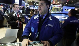 Specialist Ronnie Howard, center, works on the floor of the New York Stock Exchange, Tuesday, Jan. 5, 2016. U.S. stocks are opening modestly higher as trading stabilizes a day after a plunge in China unsettled investors around the globe. (AP Photo/Richard Drew)