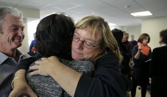 Katie Wales Lovkay, of Granby, Conn., right, who attended St. George's School from 1977-1980, hugs a former classmate, following a news conference, Tuesday, Jan. 5, 2016, in Boston. (AP Photo/Steven Senne) ** FILE **