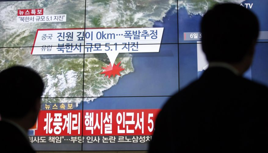 People in Seoul, South Korea, walk by a screen showing the news reporting about an earthquake near North Korea's nuclear facility on Jan. 6. (Associated Press)