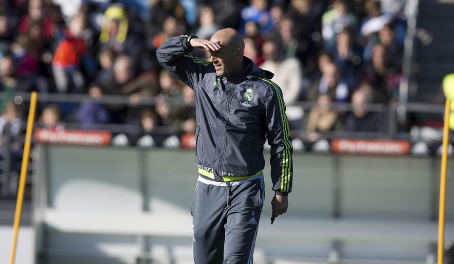 Real Madrid's newly appointed coach Zinedine Zidane shields his eyes from the sun during his first training session in Madrid, Spain, Tuesday Jan. 5, 2016. Real Madrid fired coach Rafael Benitez Monday after seven months and replaced him with former player Zinedine Zidane a day after Madrid's 2-2 draw at Valencia deepened a crisis that started with an embarrassing 4-0 home loss to rival Barcelona in November. (AP Photo/Paul White)