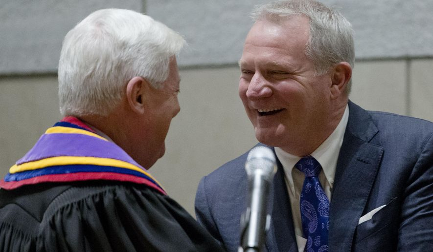 Supreme Court Chief Justice Thomas Saylor, left, greets Kevin Dougherty after he was sworn in as a Pennsylvania Supreme Court Justice Tuesday, Jan. 5, 2016, at the National Constitution Center in Philadelphia. Dougherty and other new members join a court that has been roiled by scandal in recent years. (AP Photo/Matt Rourke)