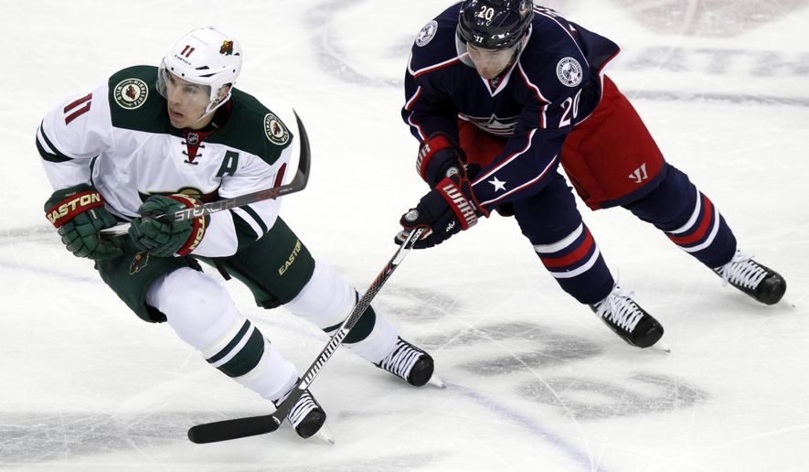Minnesota Wild's Zach Parise, left, works for the puck against Columbus Blue Jackets' Brandon Saad during the third period of an NHL hockey game in Columbus, Ohio, Tuesday, Jan. 5, 2016. Minnesota won 4-2. (AP Photo/Paul Vernon)