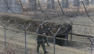 South Korean army soldiers patrol the barbed-wire fence in Paju, near the border with North Korea, South Korea, Wednesday, Jan. 6, 2016. North Korea said it conducted a powerful hydrogen bomb test Wednesday, a defiant and surprising move that, if confirmed, would be a huge jump in Pyongyang's quest to improve its still-limited nuclear arsenal. (AP Photo/Ahn Young-joon)