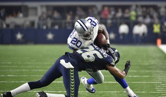 Seattle Seahawks cornerback Cary Williams (26) tackles Dallas Cowboys running back Darren McFadden (20) during an NFL football game Sunday, Nov. 1, 2015, in Arlington, Texas. (AP Photo/Michael Ainsworth)