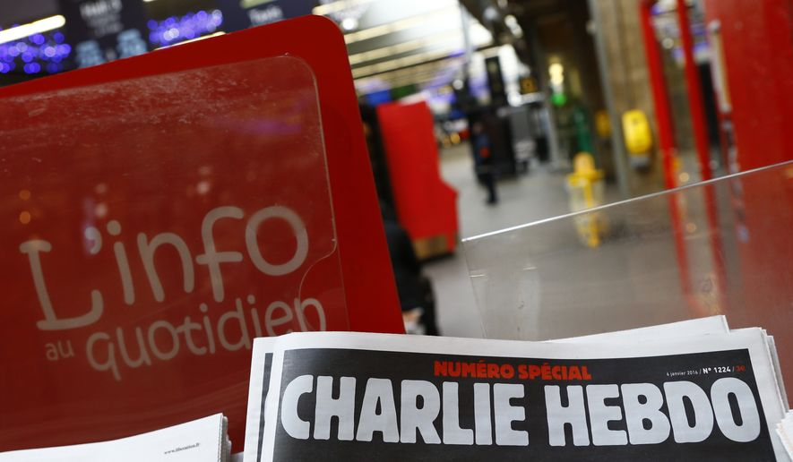 "A special edition of the satirical newspaper Charlie Hebdo that marks one year after, ""1 an apres"" the attacks on it, on a newsstand Wednesday, Jan. 6, 2016 at a train station in Paris. Seventeen people died in the attacks on Charlie Hebdo on Jan. 7, 2015, and a kosher supermarket two days later. All three attackers died. (AP Photo/Francois Mori)"