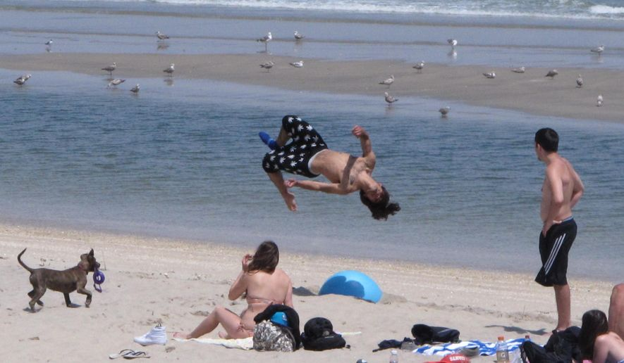 This May 15, 2015 photo shows a group of beachgoers practicing somersaults on the beach in Sea Bright, N.J. Two New Jersey lawmakers plan to introduce a bill on Thursday, Jan. 7, 2016, to restore public beach access regulations that were struck down by an appeals court in December. (AP Photo/Wayne Parry)