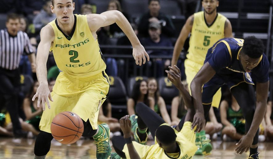 Oregon's Casey Benson, left, dribbles the ball after Oregon's Chris Boucher, center, and California's Jaylen Brown, right, stumbled while competing for the ball during the first half of an NCAA college basketball game Wednesday, Jan. 6, 2016, in Eugene, Ore. (AP Photo/Ryan Kang)