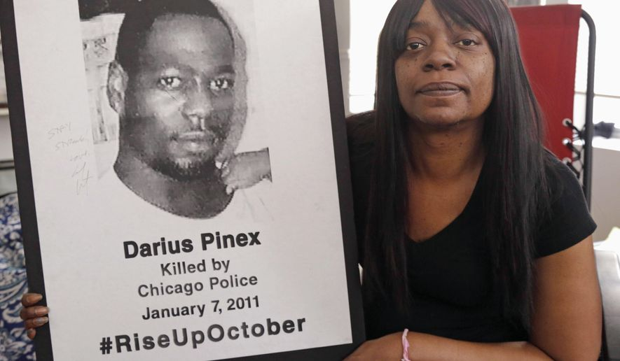 FILE - In this Dec. 17, 2015 file photo, Gloria Pinex holds a photo of her son, Darius Pinex, at her home in Chicago. Pinex sued the city after her son was killed by police in 2011 and on Monday, Jan. 4, 2016, a judge accused a city prosecutor of lying, prompting the city's law department to examine dozens of other cases the attorney worked on. (AP Photo/M. Spencer Green, File)