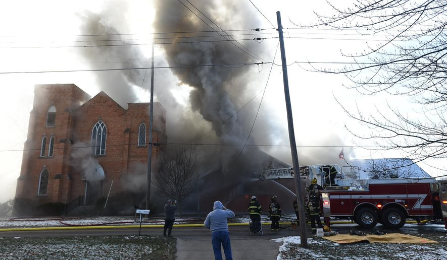 Firefighters from multiple departments in Jackson and Washtenaw counties work at the scene of a fire at the Federated Church of Grass Lake in Grass Lake, Mich., on Wednesday morning, Jan. 6, 2016. The fire caused extensive damage to the structure. No injuries were reported and there was no immediate word from officials about the cause of the fire. (J. Scott Park/Jackson Citizen Patriot via AP)