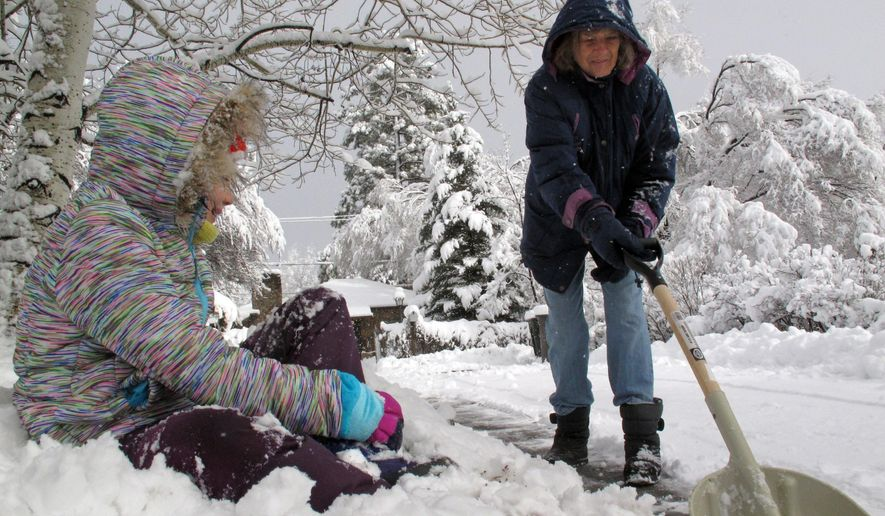 Pearl Garner, left, watches as Marilyn Anderson, right, shovels snow from the sidewalk outside their homes, Wednesday, Jan. 6, 2016 in Flagstaff, Ariz. A series of El Nino-related storms dumped heavy snow on the region. (AP Photo/Felicia Fonseca)