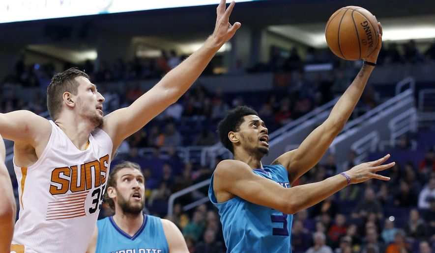 Charlotte Hornets' Jeremy Lamb, right, drives past Phoenix Suns' Mirza Teletovic (35), of Bosnia, for a score as Hornets' Spencer Hawes, middle, watches during the first half of an NBA basketball game Wednesday, Jan. 6, 2016, in Phoenix. (AP Photo/Ross D. Franklin)