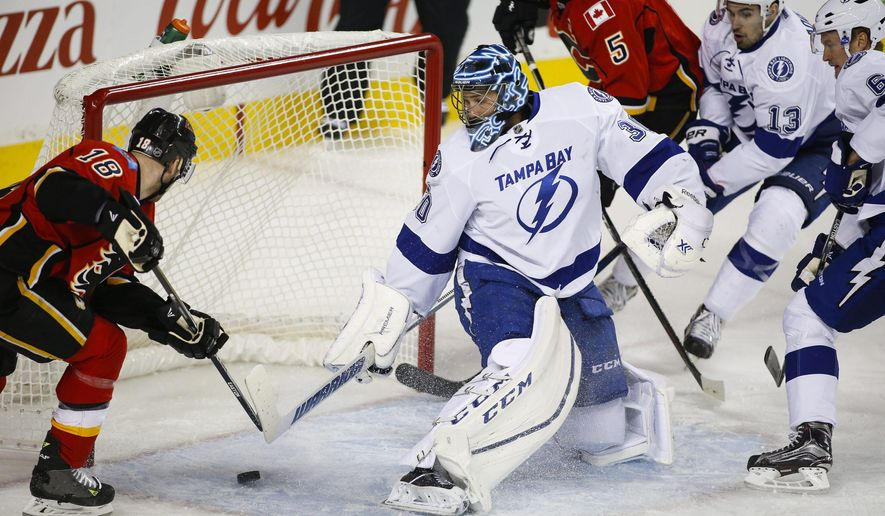 Tampa Bay Lightning goalie Ben Bishop, centre, looks back as Calgary Flames' Matt Stajan scores during first period NHL hockey action in Calgary, Alberta, Tuesday, Jan. 5, 2016. (Jeff McIntosh/The Canadian Press via AP) MANDATORY CREDIT