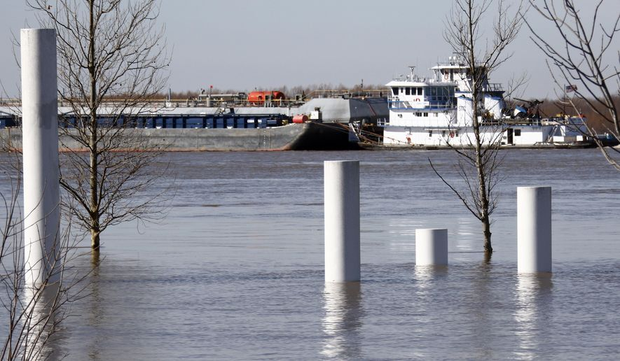 A barge and its motor escort pushes through the high water of the Mississippi River in Robinsonville, Miss., Wednesday, Jan. 6, 2016. The steel pillars in the foreground represent the different flood levels recorded at the Tunica Riverpark. The National Weather Service predicts a slightly lower crest than earlier estimates. (AP Photo/Rogelio V. Solis)